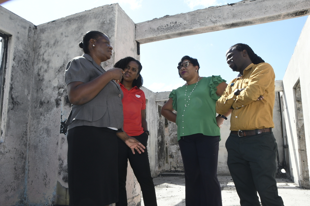 Nadeen Waugh (left), director of National Children's Home takes the Salada Foods Jamaica Team -- (from second left) Tamii Brown, commercial and corporate affairs manager; Dianna Blake Bennett, general manager; Marvin Kerr, marketing coordinator -- on a tour of the recently fire damaged facilities of the Jamaica National Children's Home.