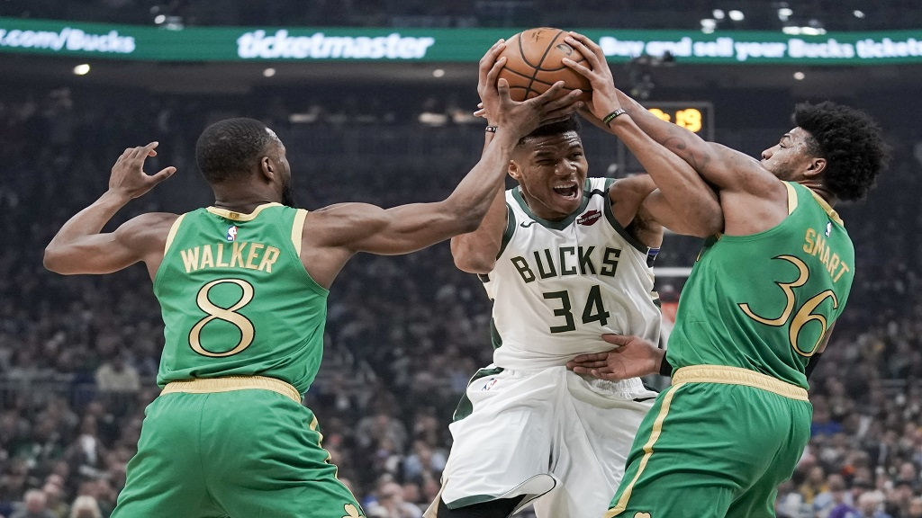 Milwaukee Bucks' Giannis Antetokounmpo tries to drive between Boston Celtics' Kemba Walker and Marcus Smart during the first half of an NBA basketball game Thursday, Jan. 16, 2020, in Milwaukee. (AP Photo/Morry Gash).