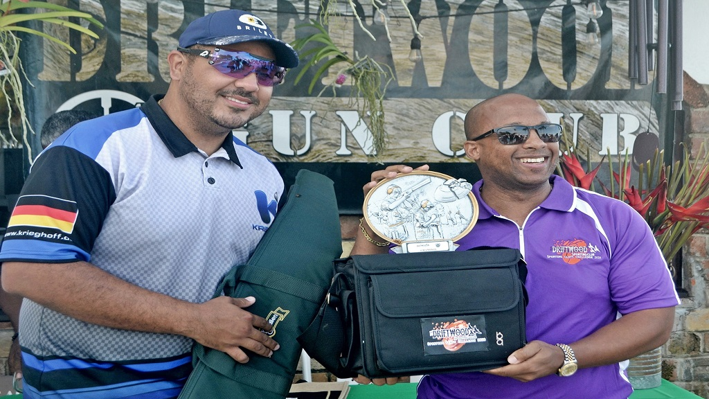 Christian Sasso (left) collects his prize from Pierre Shirley, Executive Vice President of First Rock Capital Holdings Ltd., after winning the  Driftwood Gun Club Sporting Clay competition over the weekend at Murphy Hill in St Ann.