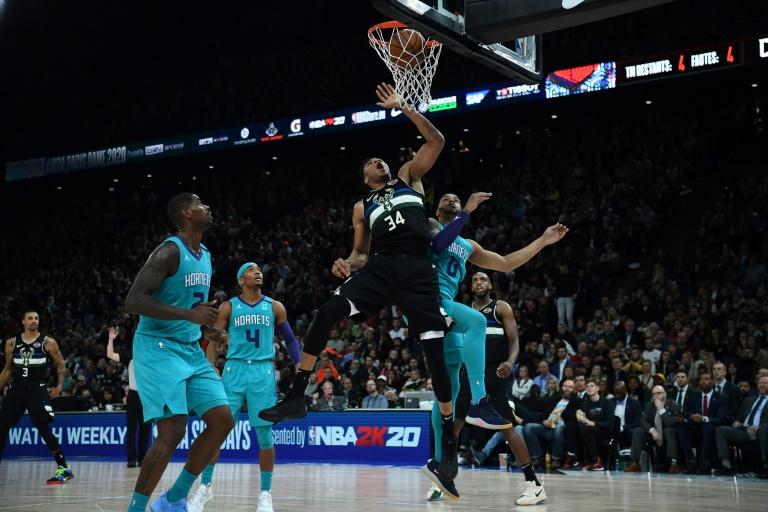 La star des Milwaukee Bucks Giannis Antetokounmpo (C) claque un dunk malgré trois joueurs des Charlotte Hornets en défense, le 24 janvier 2020 à Paris