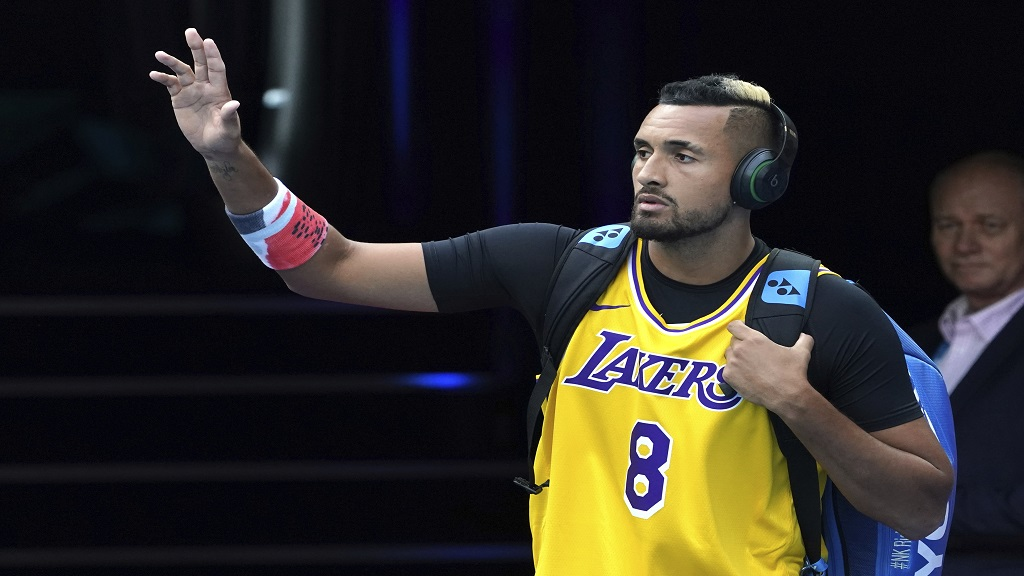 Australia's Nick Kyrgios walks onto Rod Laver Arena wearing a shirt as a tribute to Kobe Bryant ahead of his fourth round singles match against Spain's Rafael Nadal at the Australian Open tennis championship in Melbourne, Australia, Monday, January 27, 2020. (AP Photo/Lee Jin-man)