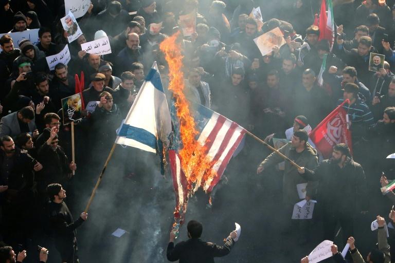 Des Iraniens brûlent des drapeaux américain et israélien le 6 janvier dans la capitale Téhéran, parmi la foule rassemblée pour rendre hommage au général Qassem Soleimani, tué dans une frappe américaine à Bagdad