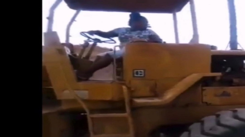 a screen grab of a 12-year-old girl calmly operating a front-end loader on a property in Jamaica.