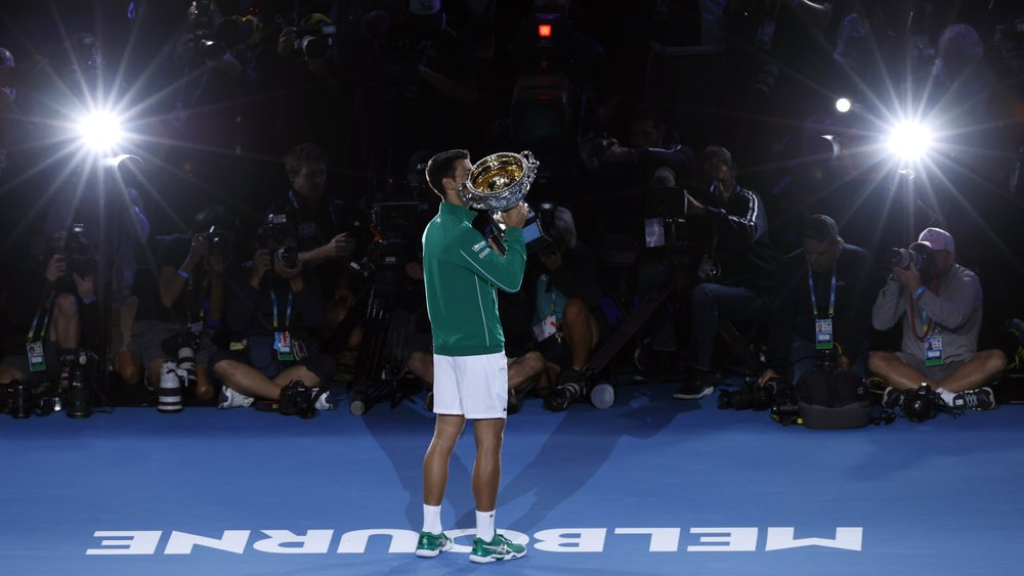Serbia's Novak Djokovic kisses the Norman Brookes Challenge Cup after defeating Austria's Dominic Thiem in the final of the Australian Open tennis championship in Melbourne, Australia, early Monday, Feb. 3, 2020. (AP PhotoDita Alangkara)