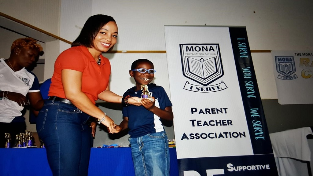 Dionne Smallhorne, Operations Manager, Express Canteen Services, makes a presentation to one of the many budding chess players at the Rapid Chess Tournament, which was hosted recently by Mona Prep School PTA at Hope United Church, Old Hope Road.