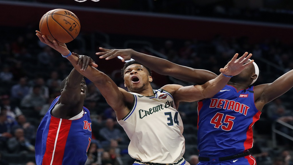 Milwaukee Bucks forward Giannis Antetokounmpo (34) makes a layup as Detroit Pistons forwards Thon Maker, left, and Sekou Doumbouya (45) defend during the first half of an NBA basketball game, Thursday, Feb. 20, 2020, in Detroit. (AP Photo/Carlos Osorio).