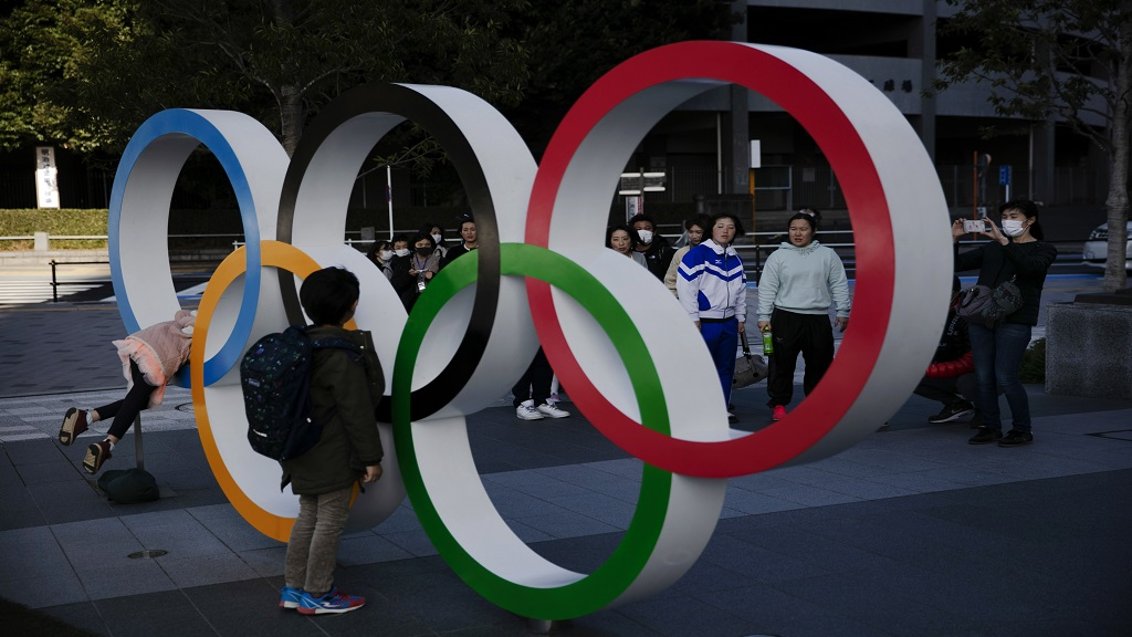 People wait in line to take pictures with the Olympic rings near the New National Stadium, Sunday, Feb. 23, 2020, in Tokyo. (AP Photo/Jae C. Hong).