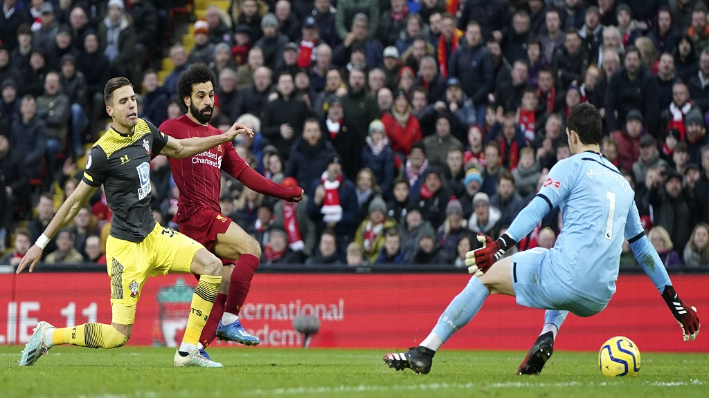 Liverpool's Mohamed Salah, centre, takes a shot past Southampton's Jan Bednarek, left, and goalkeeper Alex McCarthy during their English Premier League football match at Anfield Stadium, Liverpool, England, Saturday, February 1, 2020. (AP Photo/Jon Super).