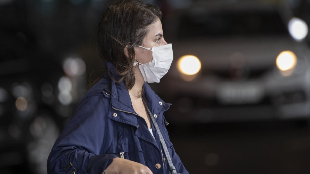 A passenger wearing a mask as a precaution against the spread of the new coronavirus COVID-19 arrives to the Sao Paulo International Airport in Sao Paulo, Brazil, Wednesday, Feb. 26, 2020. (AP Photo/Andre Penner)