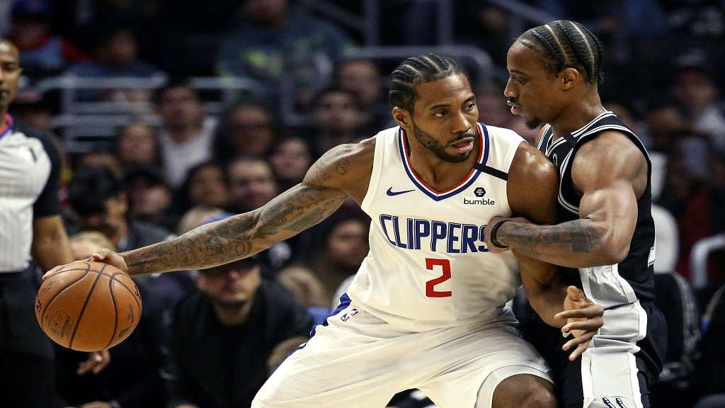 Los Angeles Clippers' Kawhi Leonard (2) is defended by San Antonio Spurs' DeMar DeRozan (10) during the first half of an NBA basketball game, Monday, Feb. 3, 2020, in Los Angeles. (AP Photo/Ringo H.W. Chiu).