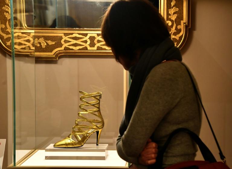 """Une visiteuse de l'exposition """"Aux pieds des dieux"""" admire une chaussure au Palais Pitti de Florence, le 30 janvier 2020 en Italie."""