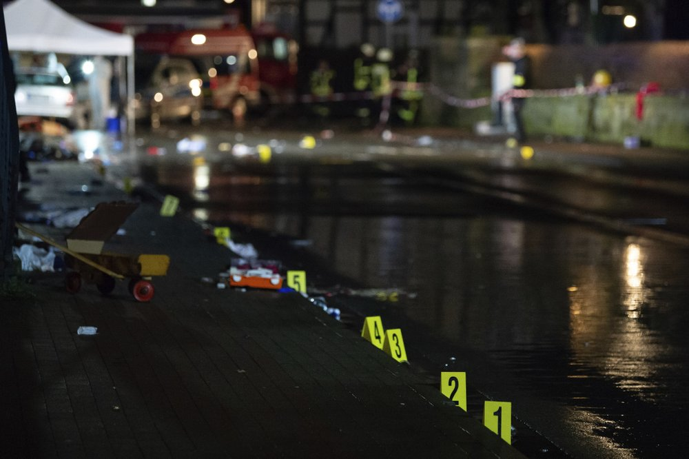 Investigators' markings are seen near the car that drove into a crowd of people during a carnival procession in Volkmarsen, Germany, Monday, Feb. 24, 2020. A man intentionally drove a car into a crowd of people at a Carnival parade in a small town in central Germany, injuring dozens of people including children, officials said Monday. (Swen Pfortner/dpa via AP)