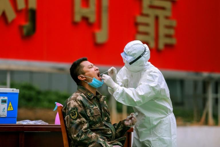 Un agent sanitaire effectue un prélèvement sur un membre de la police militaire pour un test au coronavirus, le 11 février 2020 à Shenzhen, en Chine