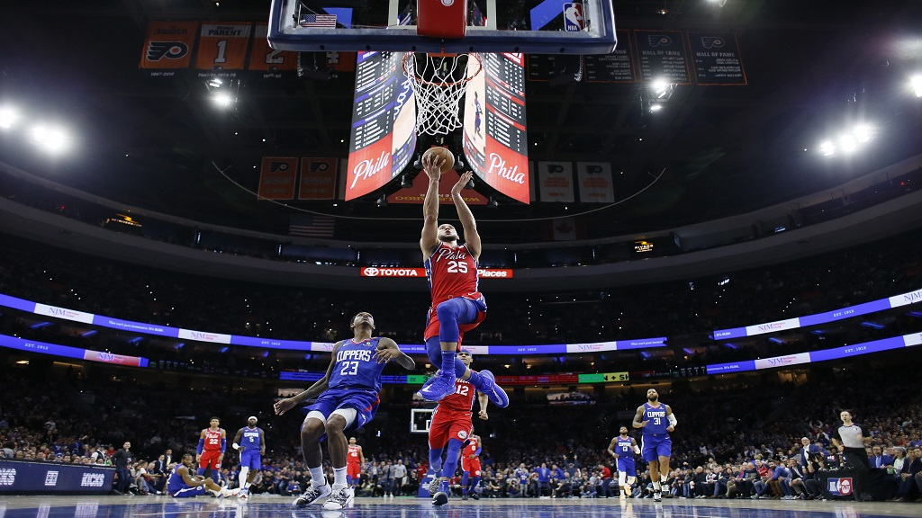 Philadelphia 76ers' Ben Simmons (25) goes up for a shot past Los Angeles Clippers' Lou Williams (23) during the first half of an NBA basketball game, Tuesday, Feb. 11, 2020, in Philadelphia. (AP Photo/Matt Slocum).