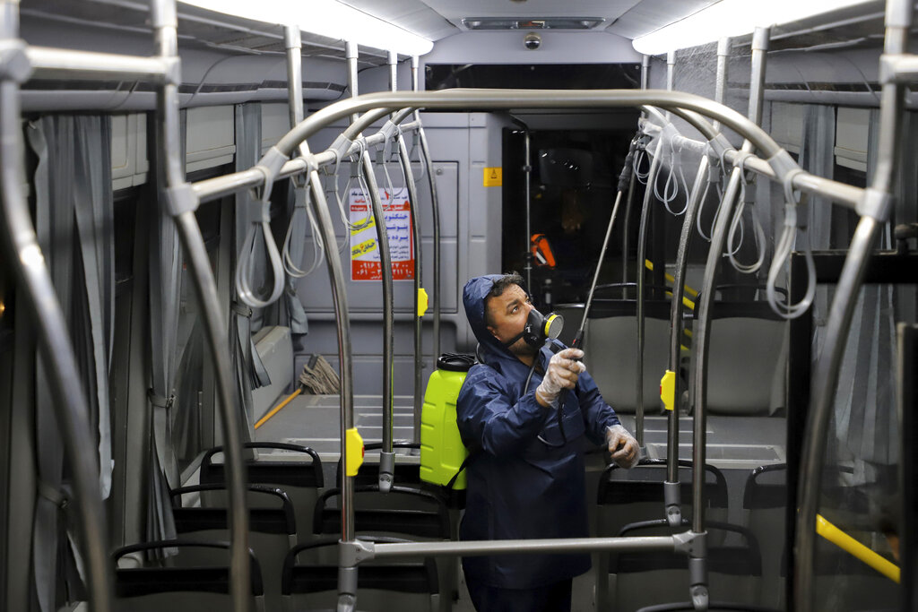 A worker disinfects a public bus against coronavirus in the city of Ahvaz in southwestern, Iran, in early morning of Tuesday, Feb. 25, 2020. Iran's government said Tuesday that more than a dozen people had died nationwide from the new coronavirus, rejecting claims of a much higher death toll of 50 by a lawmaker from the city of Qom that has been at the epicenter of the virus in the country. (Alireza Mohammadi/ISNA via AP)