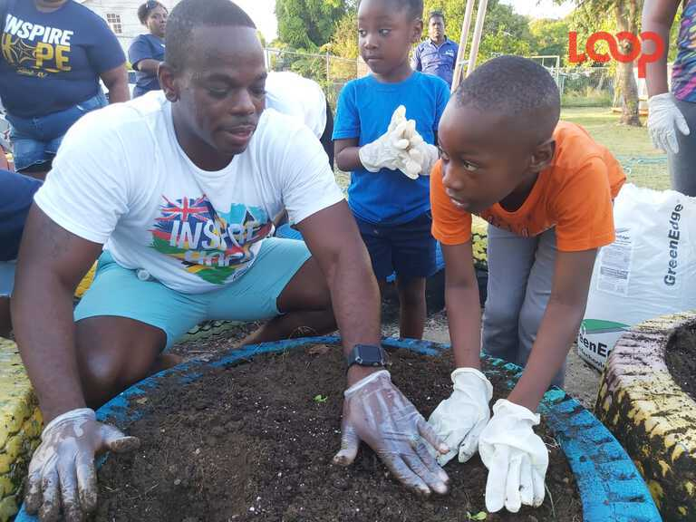 Sandals' Operation Manager Nicholas Jordan showing Keyondre (R) and Keyanah Callender of the Half Moon Fort Primary School how to plant the seedlings.