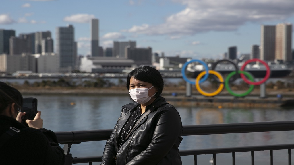In this Jan. 29, 2020, file photo, a tourist wearing a mask poses for a photo with the Olympic rings in the background, at Tokyo's Odaiba district. Tokyo Olympic organisers repeated their message at the start of two days of meetings with the IOC: this summer's games will not be cancelled or postponed by the coronavirus spreading neighboring China. (AP Photo/Jae C. Hong, File).