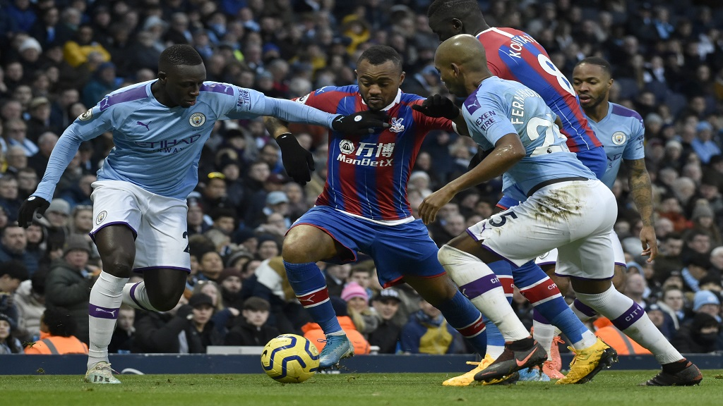 Crystal Palace's Jordan Ayew, centre, duels for the ball with Manchester City's Benjamin Mendy, left, and Fernandinho during their English Premier League football match  at Etihad stadium in Manchester, England, Saturday, Jan. 18, 2020. (AP Photo/Rui Vieira).
