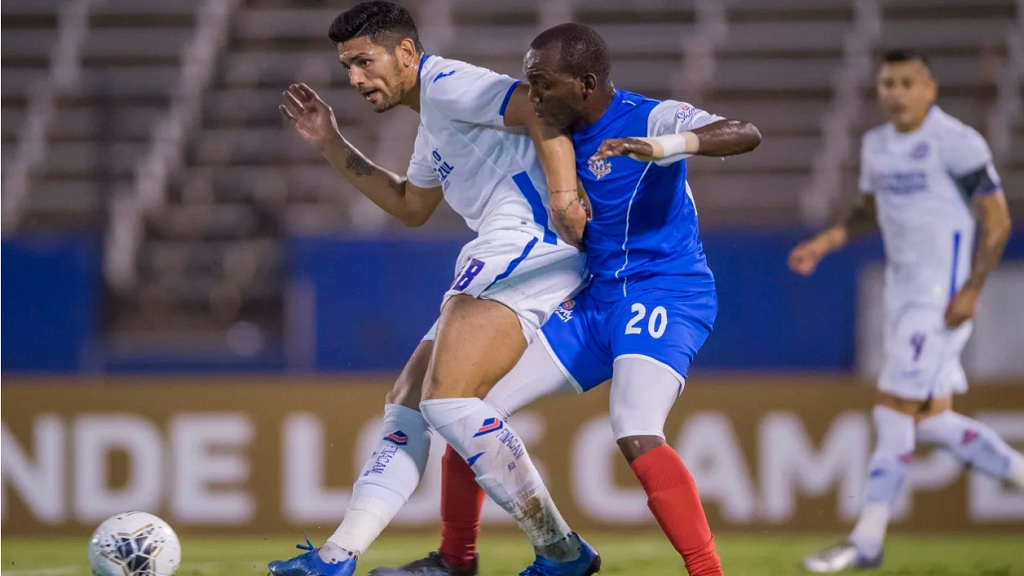 Lucas Passerini (leff) of Cruz Azul and Rondee Smith of Portmore United, fight for possession in the first leg of the Scotiabank Concacaf Champions League Round of 16 tie on February 18, 2020 at the National Stadium in Kingston. (PHOTO: Concacaf).