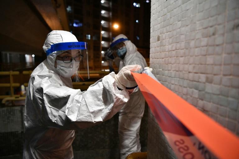 Des policiers en combinaison de protection installent un cordon sanitaire autour d'un immeuble d'habitation après deux cas de contamination à deux étages différents, le 11 février 2020 à Hong Kong