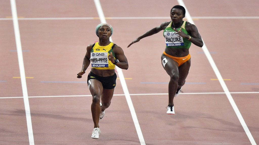 Shelly-Ann Fraser-Pryce (left), of Jamaica, and Murielle Ahouré, of the Ivory Coast compete in the women's 100m semifinal during the World Athletics Championships in Doha, Qatar, Sunday, Sept. 29, 2019. (AP Photo/Martin Meissner).