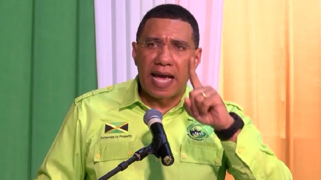Prime Minister and JLP leader Andrew Holness gestures while speaking at a political meeting on Sunday.