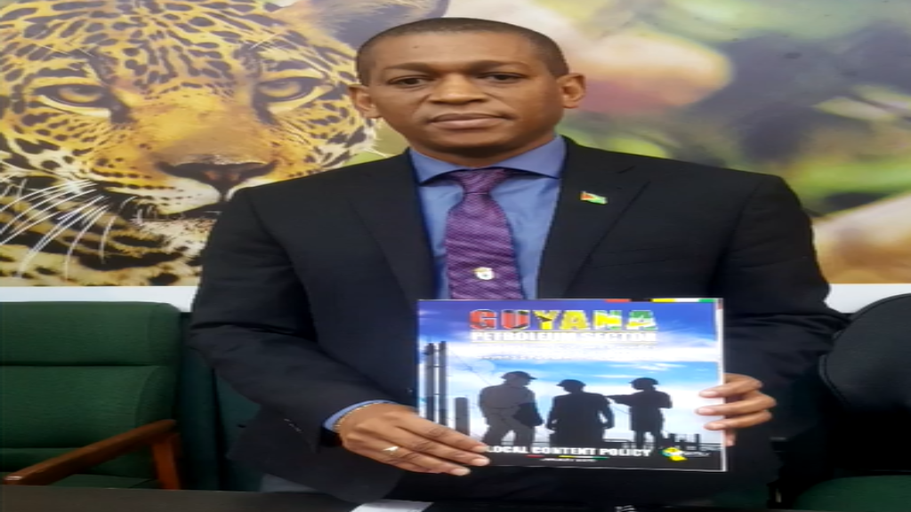 Head of Department of Energy Dr Mark Bynoe holding his copy of the Local Content Policy for Guyana's oil and gas sector.