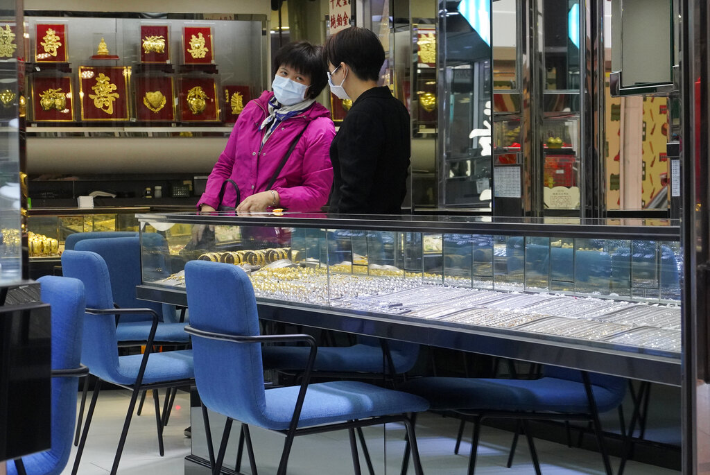 Employees wearing protective face masks at a jewellery shop in Hong Kong, Monday, Feb. 10, 2020. (AP Photo/Vincent Yu)