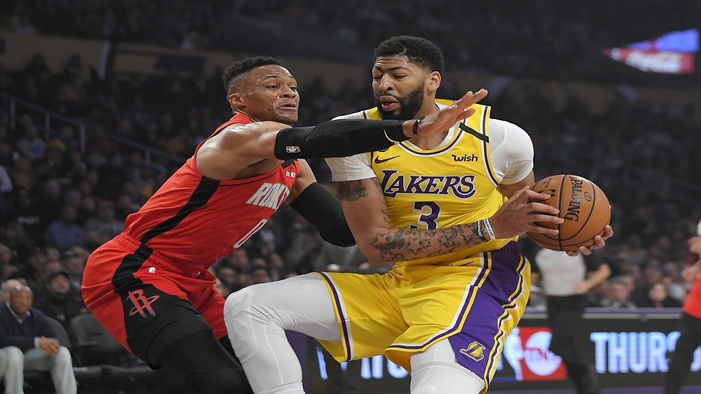 Houston Rockets guard Russell Westbrook, left, reaches for the ball held by Los Angeles Lakers forward Anthony Davis during the first half of an NBA basketball game Thursday, Feb. 6, 2020, in Los Angeles. (AP Photo/Mark J. Terrill).