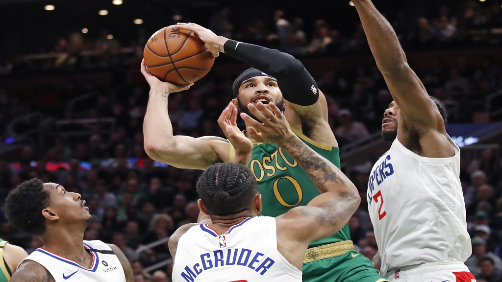 Boston Celtics forward Jayson Tatum (0) goes up to shoot against Los Angeles Clippers', from left to right, Lou Williams, Rodney McGruder and Kawhi Leonard in the first half of an NBA basketball game, Thursday, Feb. 13, 2020, in Boston. (AP Photo/Elise Amendola).