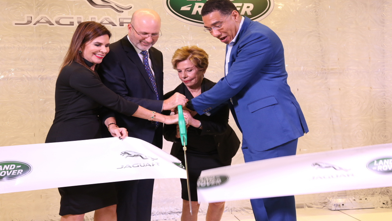 Prime Minister Andrew Holness (right) assists Stewart's Automotive Group executives (from left) Jackie Stewart Lechler; Duncan Stewart and Diana Stewart in the ribbon-cutting ceremony for the state-of-the-art showroom for its Jaguar Land Rover brands.