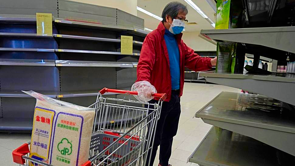 A man wearing face mask and plastic bag as a glove walks past empty shelf of tissue papers at a supermarket in Hong Kong, Friday, Feb. 7, 2020. In recent days, residents have been buying large amounts of products because they fear that border restrictions, which were enforced to control the coronavirus outbreak, may affect supply flows into Hong Kong. (AP Photo/Kin Cheung
