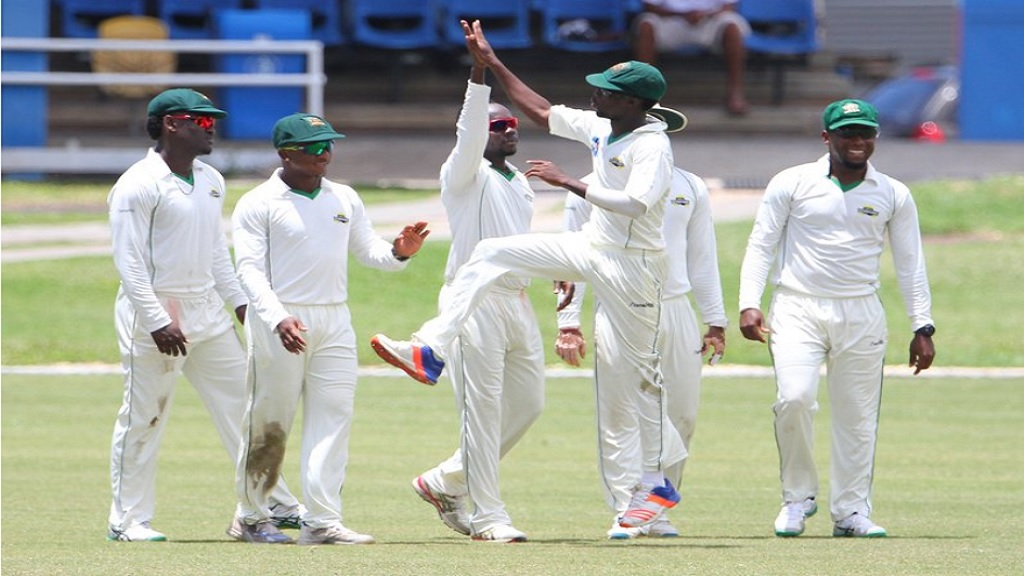 Jamaica Scorpions players celebrate the fall of a wicket.
