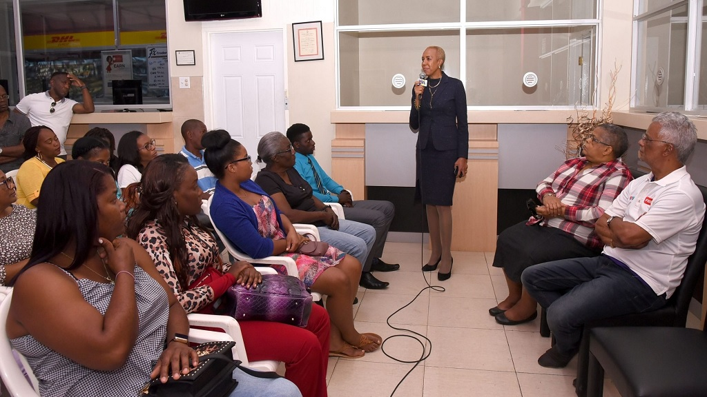 Minister of Science, Energy and Technology, Fayval Williams (standing), addresses staff members of Heaven's Fesco Gas Station in Mandeville on Sunday, February 23. Also pictured at right are owner of the station, Trevor Heaven, and Permanent Secretary in the ministry, Carol Palmer. (Photo: JIS)