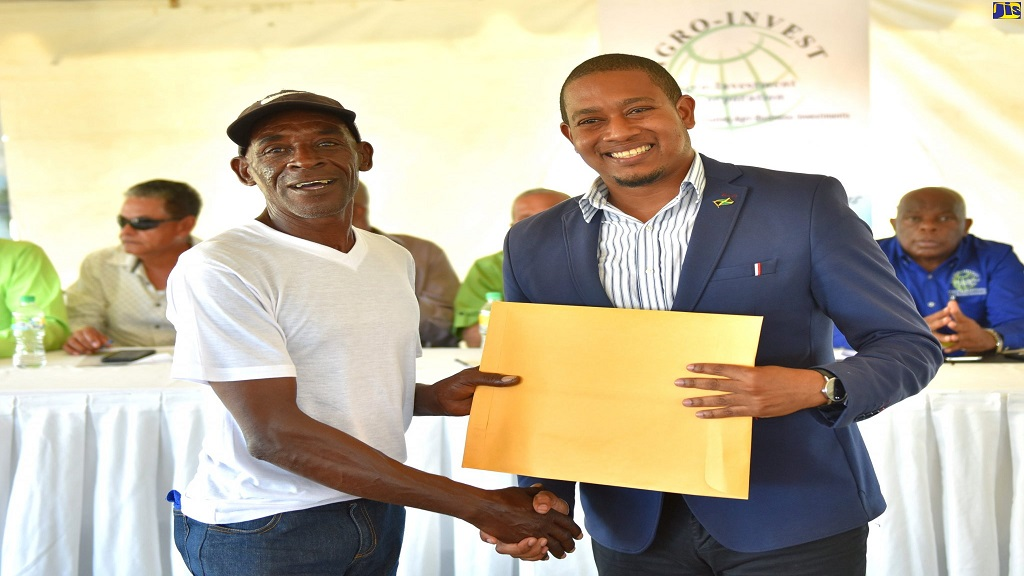 State Minister in the Ministry of Industry, Commerce, Agriculture and Fisheries, Floyd Green (right), presents a land lease document to Trevor Morris, former worker at Monymusk Sugar Factory in Clarendon, on February 20.