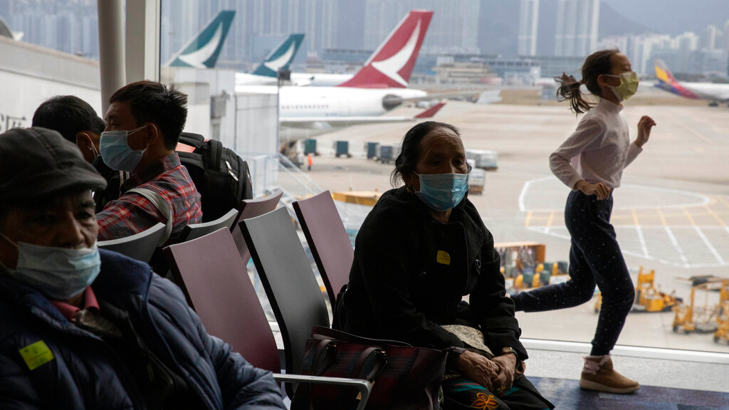 A child runs past passengers wearing masks waiting for their flight in Hong Kong on Sunday, February 9, 2020. China's virus death toll rose above 800, passing the number of fatalities in the 2002-2003 SARS epidemic, but fewer new cases were reported in a possible sign its spread may be slowing as other nations step up efforts to block the disease. (AP Photo/Ng Han Guan)