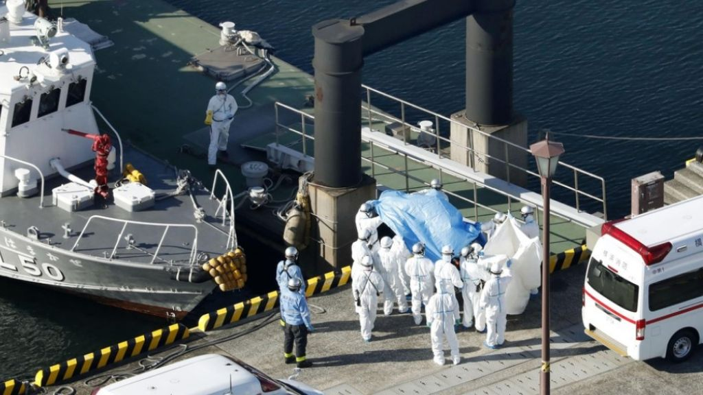 Medical workers in protective suits lead a passenger tested positive for a new coronavirus from the cruise ship Diamond Princess at Yokohama Port in Yokohama, south of Tokyo, Wednesday, February 5, 2020. (Hiroko Harima/Kyodo News via AP)