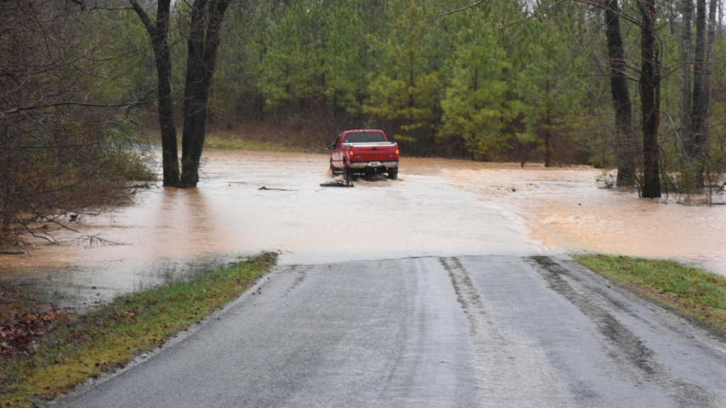 A truck drives through a pool of water on Thursday, Feb. 6, 2020, on Sandy Creek Road in Pittsylvania County, Va., which had several areas of moving water that rose as high as a few feet. (Caleb Ayers/Danville Register & Bee via AP)