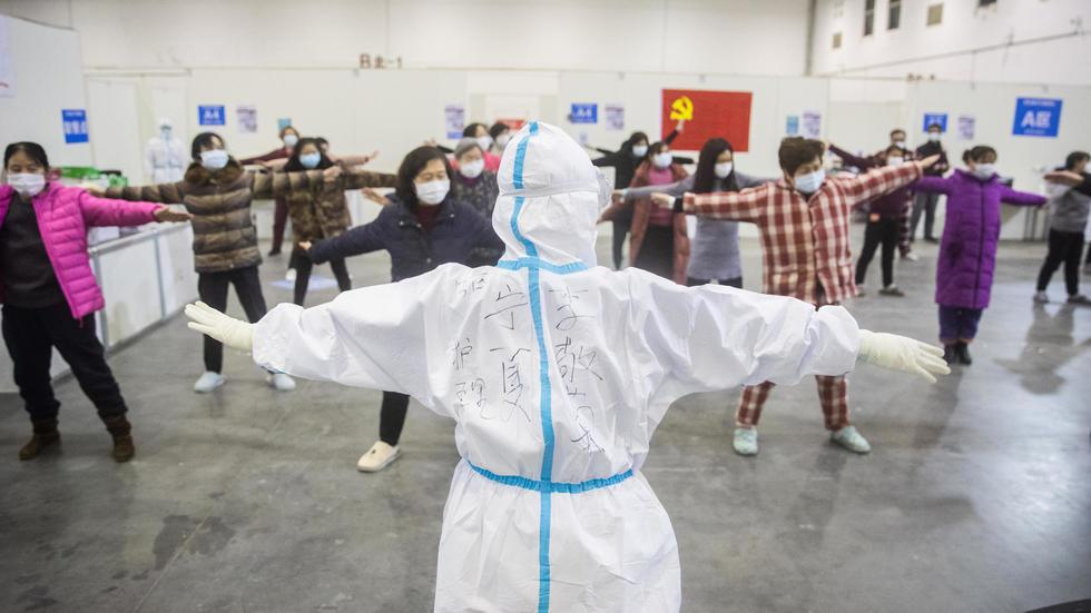 Des patients ayant des symptômes du coronavirus participent à une séance de gymnastique encadrée par du personnel médical en combinaison de protection dans un hôpital de Wuhan, le 17 février 2020 afp.com - STR