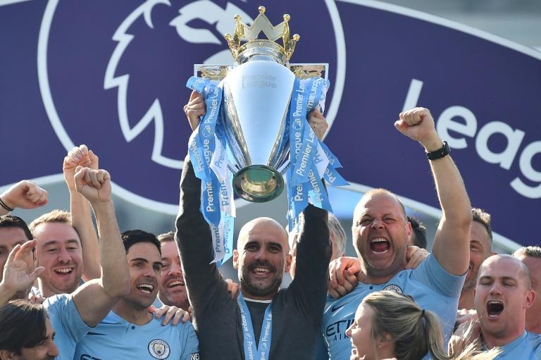 Le manager espagnol de Manchester City Pep Guardiola au milieu de ses joueurs avec le trophée de champion d'Angleterre, le 12 mai 2019 à Brighton