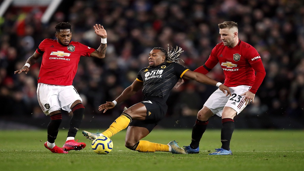 Wolverhampton Wanderers' Adama Traore battles for the ball with Manchester United's Fred, left, and Luke Shaw, right, during their English Premier League football match at Old Trafford, Manchester, England, Saturday, Feb. 1, 2020. (Martin Rickett/PA via AP).