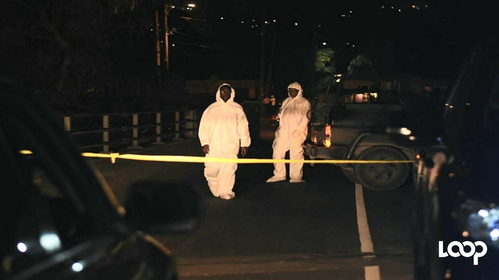Forensic team members at the scene of the crime in Ackee Walk, St Andrew on Tuesday. (Photos: Marlon Reid)