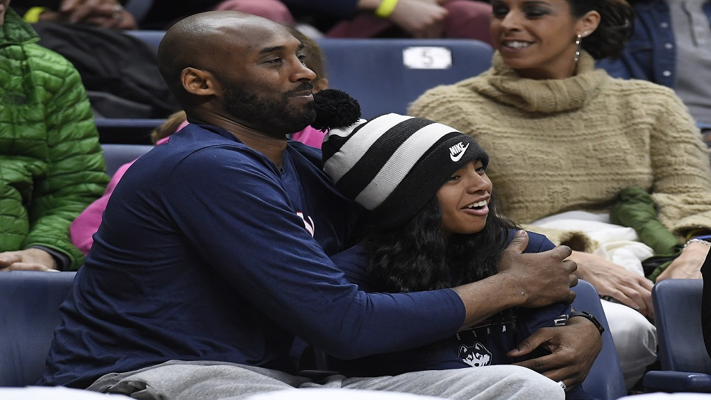 In this March 2, 2019, file photo Kobe Bryant and his daughter Gianna watch the first half of an NCAA college basketball game between Connecticut and Houston in Storrs, Conn. (AP Photo/Jessica Hill, File).