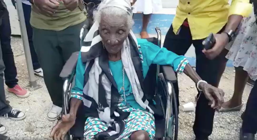 Photo illustrant  Bernicia Souffrant dite Madan Janba (Madame Jean-Ba) accrochée à son fauteuil roulant