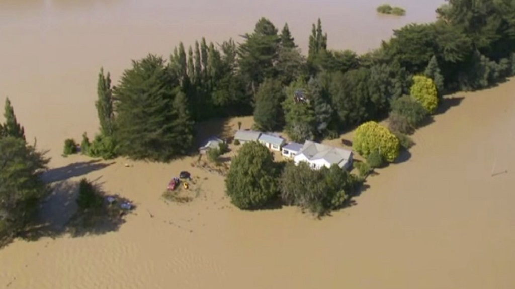 In this image made from video, a rescue helicopter, center, winches a resident to safety over floodwaters in Gore, New Zealand, Wednesday, February 5, 2020. Hundreds of people evacuated their homes and farms Wednesday to escape flooding in southern New Zealand. (Newshub via AP)