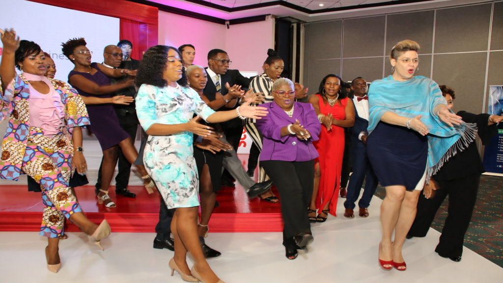 """2019 Graduates of the Scotiabank Vision Achiever Programme make a ceremonial """"woosh"""" at the final ceremony."""