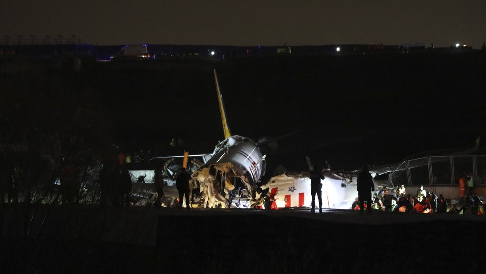 Rescue members work after a plane skidded off the runway at Istanbul's Sabiha Gokcen Airport, Wednesday, Feb. 5, 2020. A plane skidded off the runway Wednesday at Istanbul's Sabiha Gokcen Airport, crashing into a field and breaking into pieces. Passengers were seen evacuating through cracks in the plane and authorities said at least 21 people were injured. (AP Photo)