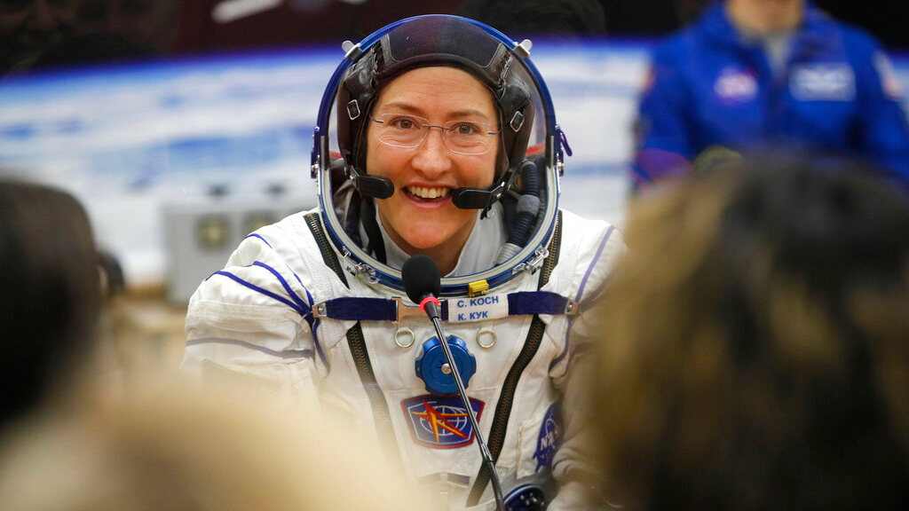 FILE - In this Thursday, March 14, 2019 file photo, US astronaut Christina Koch, member of the main crew of the expedition to the International Space Station (ISS), speaks with her relatives through a safety glass prior the launch of Soyuz MS-12 space ship at the Russian leased Baikonur cosmodrome, Kazakhstan. (AP Photo/Dmitri Lovetsky, Pool)
