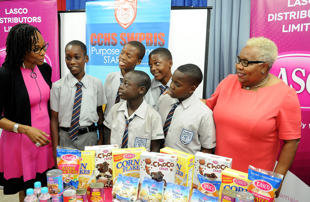 Professor Rosalea Hamilton (left), CEO of the LASCO Chin Foundation engages Chairman of Clan Carthy High School, Maxine Henry-Wilson (right); Grade 7 students during a handover of Lasco breakfast items to the school on Tuesday, January 21, 2020.