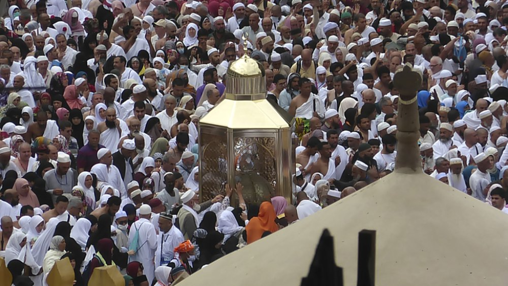 In this Feb. 24, 2020, photo, Muslim pilgrims pray near Maqam Ibrahim, or the Station of Abraham, the golden glass structure, center, at the Grand Mosque in the Muslim holy city of Mecca, Saudi Arabia. Saudi Arabia halted Thursday, Feb. 27 travel to the holiest sites in Islam over fears of the global outbreak of the new coronavirus just months ahead of the annual hajj pilgrimage, a move coming as the Mideast has over 220 confirmed cases of the illness. (AP Photo/Amr Nabil)